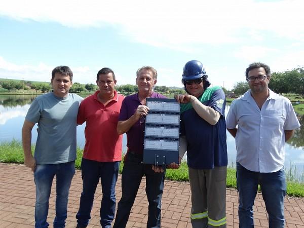 Prefeito Tide Balzanelo com a nova luminária em led em mãos e equipe técnica e servidores reunidos.. Foto: FLÁVIO ROVERATO